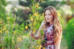 Fermez-vous vers le haut du portrait romantique de la belle femme élégante dans des arbres de ressort de fleur photos stock