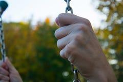 Fermez-vous vers le haut du regard sur des mains tenant les chaînes tendues de l'oscillation images stock