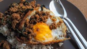 Fermez-vous vers le haut du riz complété avec du porc et le basilic hachés frits par émoi Photographie stock