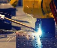 Fermez-vous vers le haut du robot industriel jaune soudant la partie des véhicules à moteur dans l'usine moderne, modifiée la ton photo stock