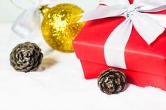 Fermez-vous vers le haut du ruban blanc de boîte-cadeau rouge avec la boule et le pin de Noël Photos stock
