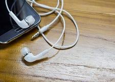 Fermez-vous vers le haut du smartphone et des écouteurs photographie stock