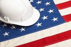 Fermez-vous vers le haut du studio tiré d'un casque blanc de construction de couleur s'étendant au-dessus du drapeau des Etats-Un Photos libres de droits
