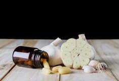 Fermez-vous vers le haut du supplément de gel de capsule d'ail et de pétrole sur le CCB en bois de blanc images stock