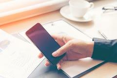 Fermez-vous vers le haut du téléphone intelligent d'utilisation d'homme d'affaires de main pour le rapport financier d'investisse Images libres de droits