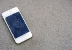 Fermez-vous vers le haut du téléphone portable moderne avec l'écran cassé sur la route goudronnée image stock