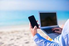Fermez-vous vers le haut du téléphone sur le fond de l'ordinateur à la plage Images libres de droits