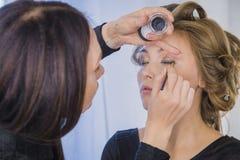 Fermez-vous vers le haut du tir Artiste de maquillage professionnel appliquant le fard à paupières Photos libres de droits