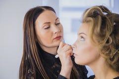 Fermez-vous vers le haut du tir Artiste de maquillage professionnel appliquant le fard à paupières Photos stock