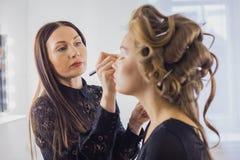 Fermez-vous vers le haut du tir Artiste de maquillage professionnel appliquant le fard à paupières Photo libre de droits