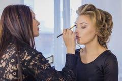 Fermez-vous vers le haut du tir Artiste de maquillage professionnel appliquant le fard à paupières Photo stock