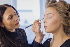 Fermez-vous vers le haut du tir Artiste de maquillage professionnel appliquant le fard à paupières Image stock