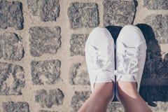 Fermez-vous vers le haut du tir cultivé des jambes du ` un s de jeune dame dans des chaussures blanches de gomme Photographie stock libre de droits