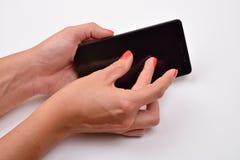 Fermez-vous vers le haut du tir d'une femme dactylographiant au téléphone portable d'isolement sur le blanc photos stock