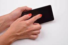 Fermez-vous vers le haut du tir d'une femme dactylographiant au téléphone portable d'isolement sur le blanc image stock