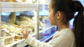Fermez-vous vers le haut du tir d'une fille assez petite posinting aux desserts à la boulangerie banque de vidéos