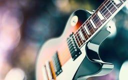 Fermez-vous vers le haut du tir d'une guitare, au-dessus de fond blured de lumières Photo stock