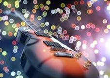 Fermez-vous vers le haut du tir d'une guitare, au-dessus de fond blured de lumières Photo libre de droits