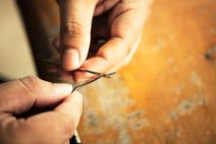 Fermez-vous vers le haut du tir de l'insertion de fil dans une aiguille sur le doigt humain Co photos libres de droits