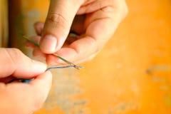Fermez-vous vers le haut du tir de l'insertion de fil dans une aiguille sur le doigt humain Co images libres de droits
