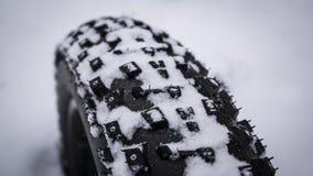 Fermez-vous vers le haut du tir de la bande de roulement sur un gros pneu de vélo de montagne dans la neige Image libre de droits