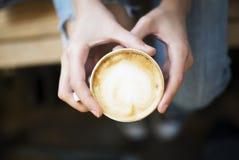 Fermez-vous vers le haut du tir de la fille tenant une tasse de café dans des ses mains Photographie stock