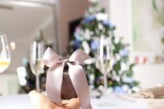 Fermez-vous vers le haut du tir de la main femelle jugeant un petit cadeau enveloppé avec r Photographie stock libre de droits