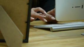 Fermez-vous vers le haut du tir de la main de femme dactylographiant sur le clavier d'ordinateur dans le bureau moderne à la tabl banque de vidéos