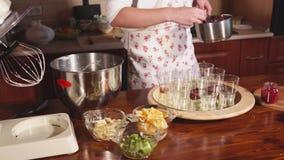 Fermez-vous vers le haut du tir de la main du ` s de chef, qui prépare un dessert fruité en verres clips vidéos