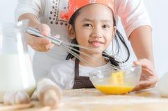 Fermez-vous vers le haut du tir de la petite fille asiatique de sourire faisant la boulangerie avec le MOIS image stock