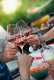 Fermez-vous vers le haut du tir des amis jetant des verres en l'air Rose Wine Photos libres de droits