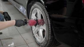 Fermez-vous vers le haut du tir des disques de lavage d'une voiture d'homme dans la lave-auto banque de vidéos