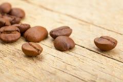 Fermez-vous vers le haut du tir des grains de café rôtis sur la vieille table en bois photographie stock