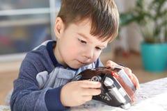 Fermez-vous vers le haut du tir des jeux masculins châtains attrayants d'enfant avec sa voiture préférée de jouet, essais pour ré photographie stock