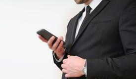 Fermez-vous vers le haut du tir des mains d'homme d'affaires tenant un téléphone sur le CCB blanc images stock