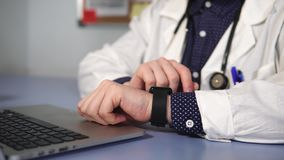 Fermez-vous vers le haut du tir du docteur utilisant la montre intelligente sur sa main fonctionnant dans son coffret banque de vidéos
