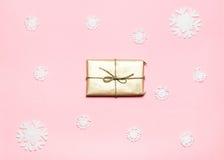 Fermez-vous vers le haut du tir du petit cadeau enveloppé avec le ruban sur les flocons de neige décorés par fond rose Noël Conce Images stock