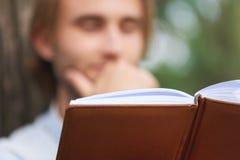 Fermez-vous vers le haut du tir L'étudiant en parc de campus a lu un livre Images stock