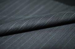 Fermez-vous vers le haut du tissu bleu d'ombre de noir de petit pain du costume photographie stock