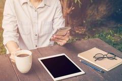 Fermez-vous vers le haut du téléphone de participation de femme de main dans le café, filtre de vintage Photos stock