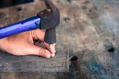 Fermez-vous vers le haut du travailleur martelant le clou dans le bois, style de vintage Photographie stock libre de droits