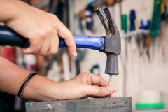 Fermez-vous vers le haut du travailleur martelant le clou dans le bois, style de vintage Photo libre de droits