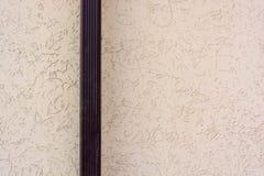 Fermez-vous vers le haut du tuyau de descente d'eaux ménagères avec la surface beige de mur images stock