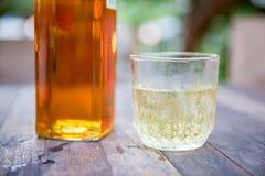 Fermez-vous vers le haut du verre de boissons alcoolisées, buvez de l'alcool bouteille sur la table en bois avec la lumière de bo photos libres de droits