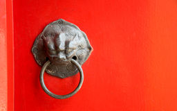 Fermez-vous vers le haut du vieux heurtoir sur la porte rouge dans le temple thaïlandais Image libre de droits