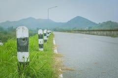 Fermez-vous vers le haut du vieux poteau noir et blanc de pilier concret près de la route avec le réservoir avec la montagne à l' photos stock