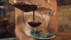 Fermez-vous vers le haut du vin de versement en verre pour la jeune femme à la table de dîner dans le restaurant Femme buvant du  clips vidéos