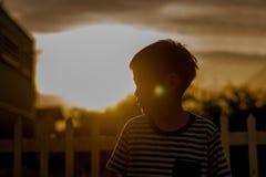 Fermez-vous vers le haut du visage heureux du garçon extérieur dans le temps de coucher du soleil noir et blanc photographie stock libre de droits