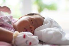 Fermez-vous vers le haut du visage nouveau-né avec la lumière du soleil Une partie de visage Nouveau-né dort Images stock