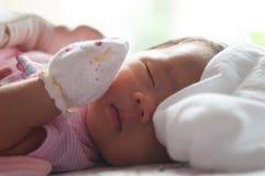 Fermez-vous vers le haut du visage nouveau-né avec la lumière du soleil Une partie de visage Nouveau-né dort Image stock